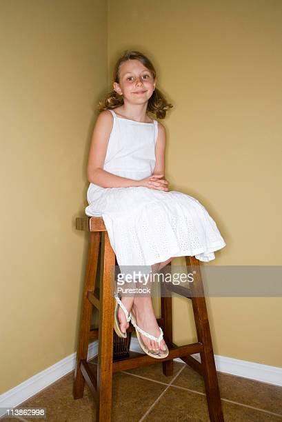 Girl sitting in corner on stool