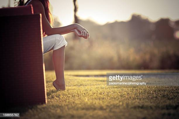 Girl sitting in countryside at sunset