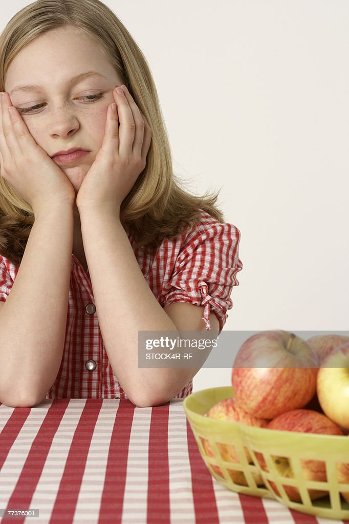 Girl sitting in front of some apples