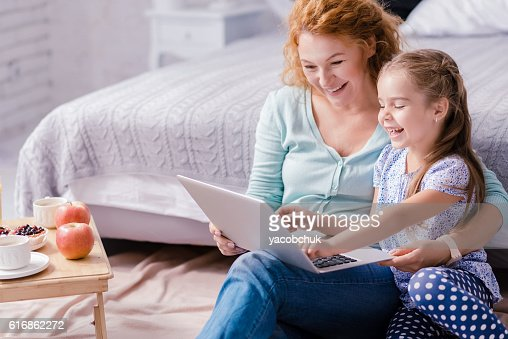 Girl sitting in front of the laptop with her grandmother : Stock Photo