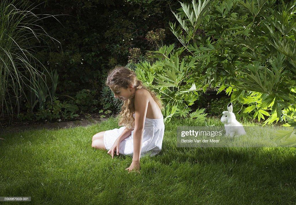 Girl (10-11) sitting in garden in front of toy rabbit