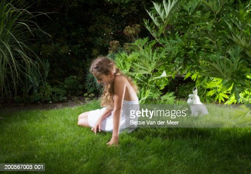 Girl (10-11) sitting in garden in front of toy rabbit