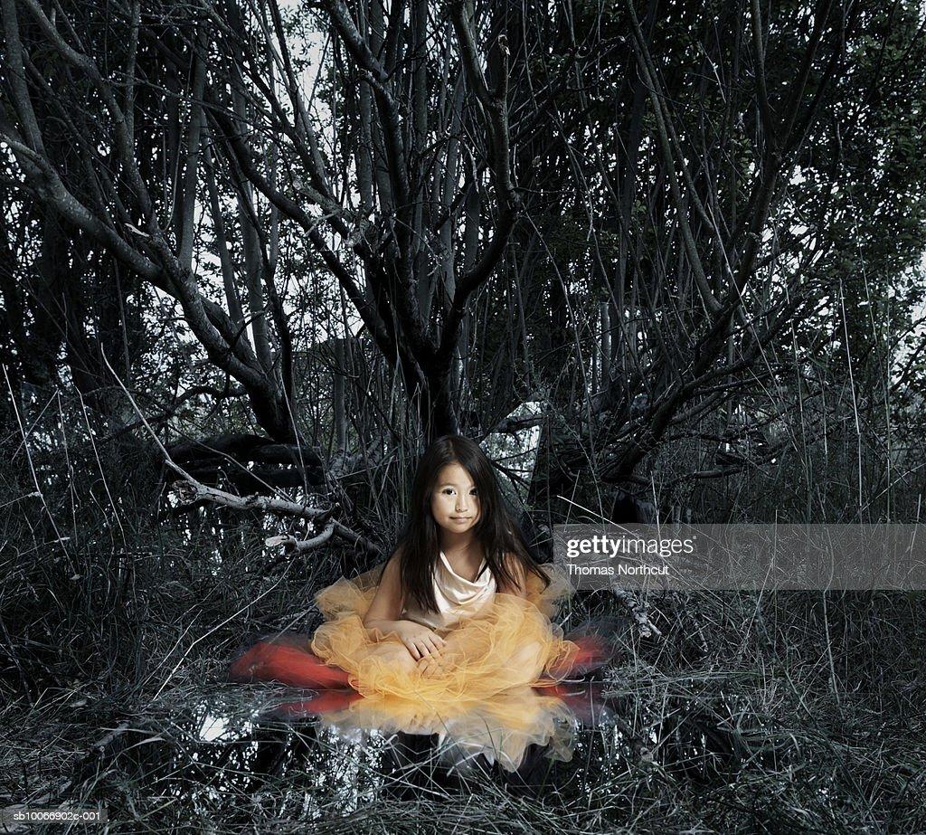 Girl (8-9) sitting in grove, portrait (Digital Composite) : Stock Photo