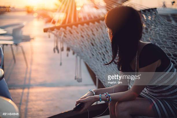 Girl sitting in hammock and watching the sunset