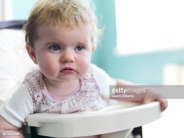 Girl sitting in high chair