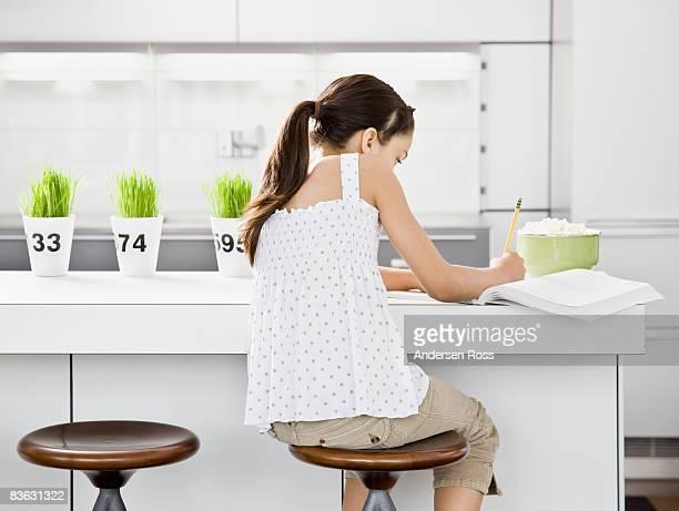 Girl sitting in kitchen doing homework
