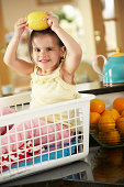 Girl Sitting In Laundry Basket On Kitchen Counter With Lemon