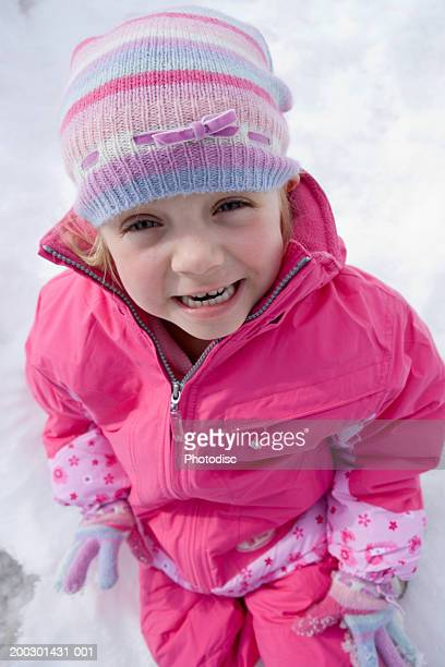 Girl (4-5) sitting in snow, portrait