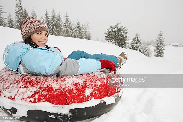 Girl sitting in snow tube
