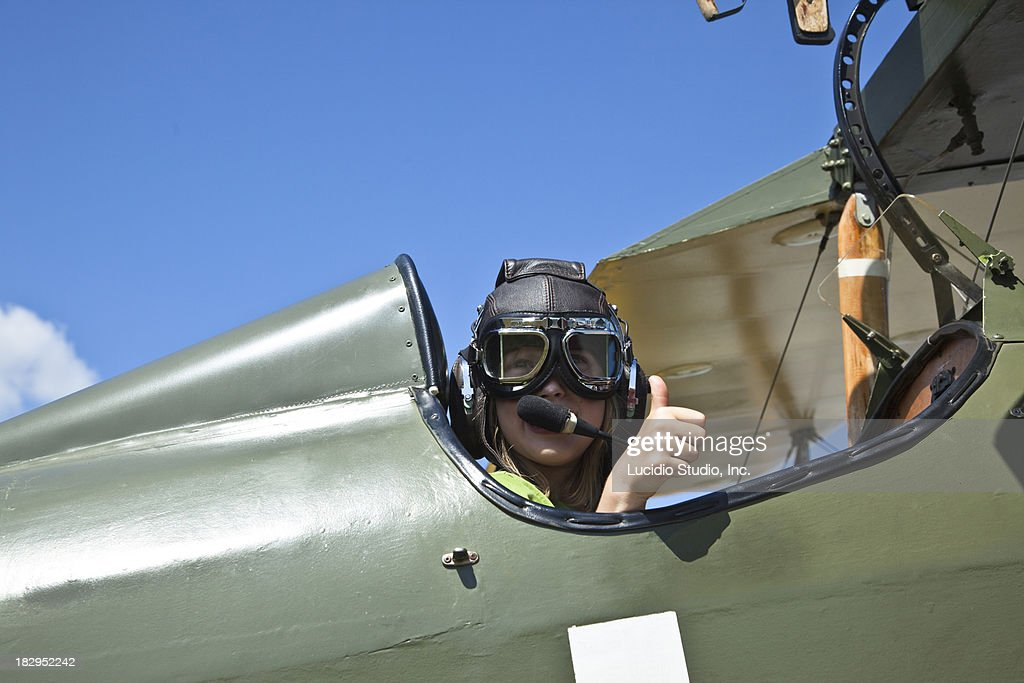 Girl sitting in the cockpit of an old biplane