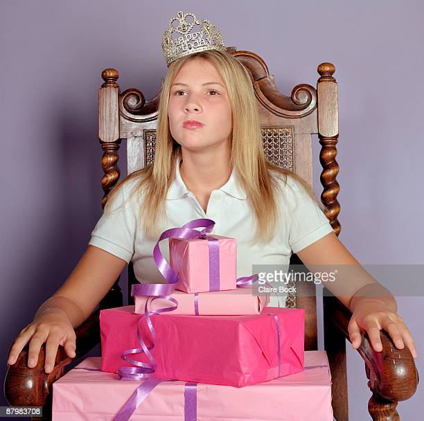 Girl sitting in throne with crown and stack of presents