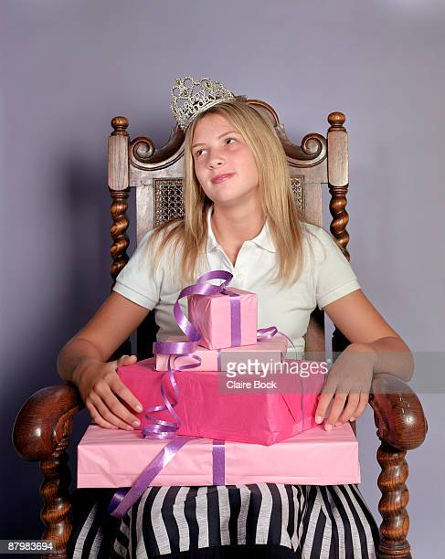 Girl sitting in throne with stack of presents and crown