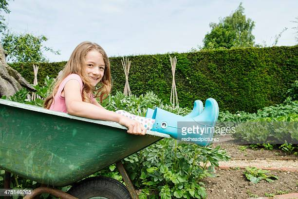 Girl sitting in wheelbarrow
