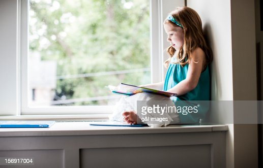 Girl Sitting In Window Reading A Book Stock Photo Getty