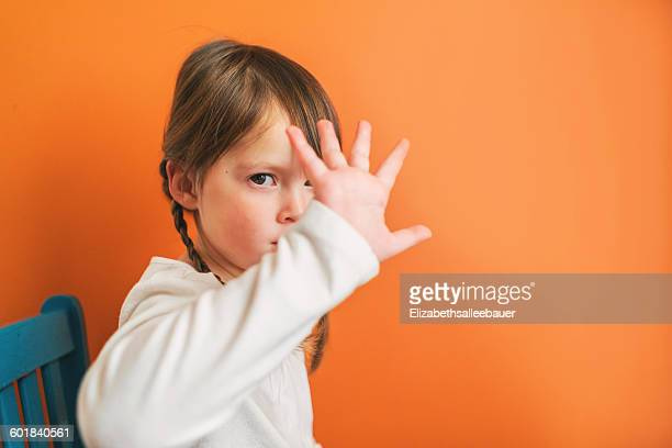 Girl sitting on a chair pouting and holding her hand in front of her face