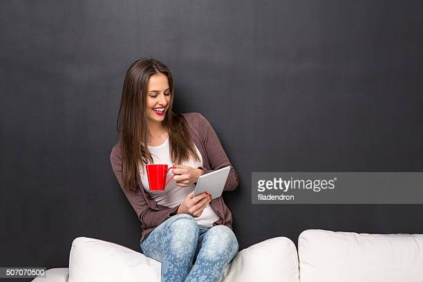 Girl sitting on a couch with a tablet