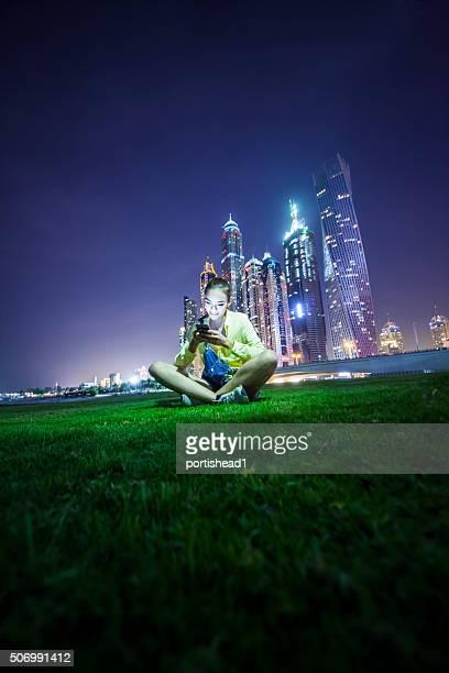 Mädchen sitzen auf Gras-Feld vor Stadtlandschaft