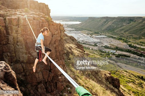 Girl sitting on a high slack line over a town.