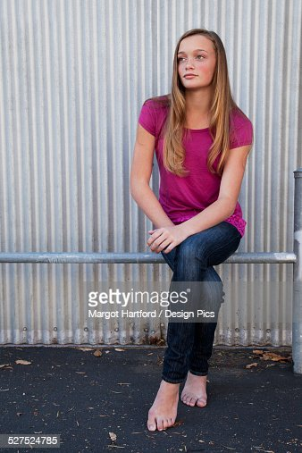 A girl sitting on a metal rail in bare feet
