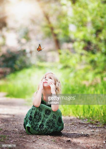 Girl sitting on a path looking at a butterfly