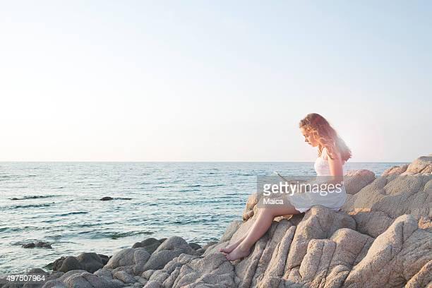 Fille assis sur un rocher au bord de la mer