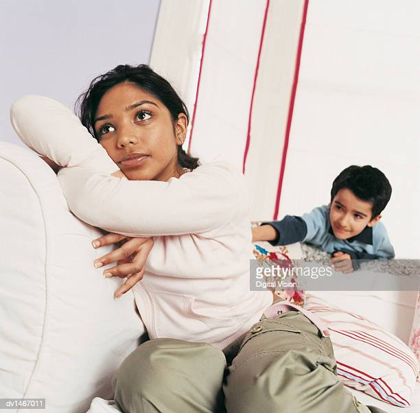 Girl Sitting on a Sofa Daydreaming and Her Younger Brother Irritating Her Behind
