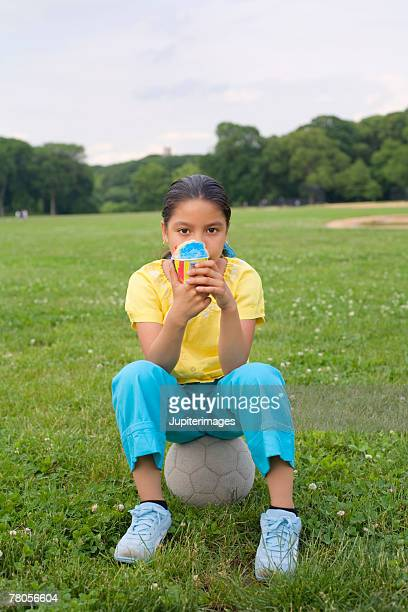 Girl sitting on ball with icy treat in park