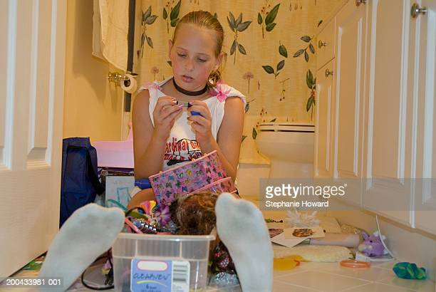 Girl (9-11) sitting on bathroom floor looking at make-up accessories