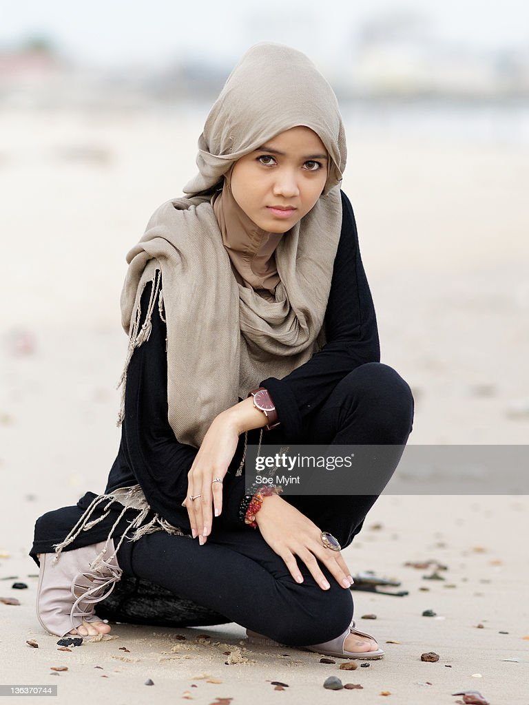 Girl sitting on beach and looking at camera : Stock Photo