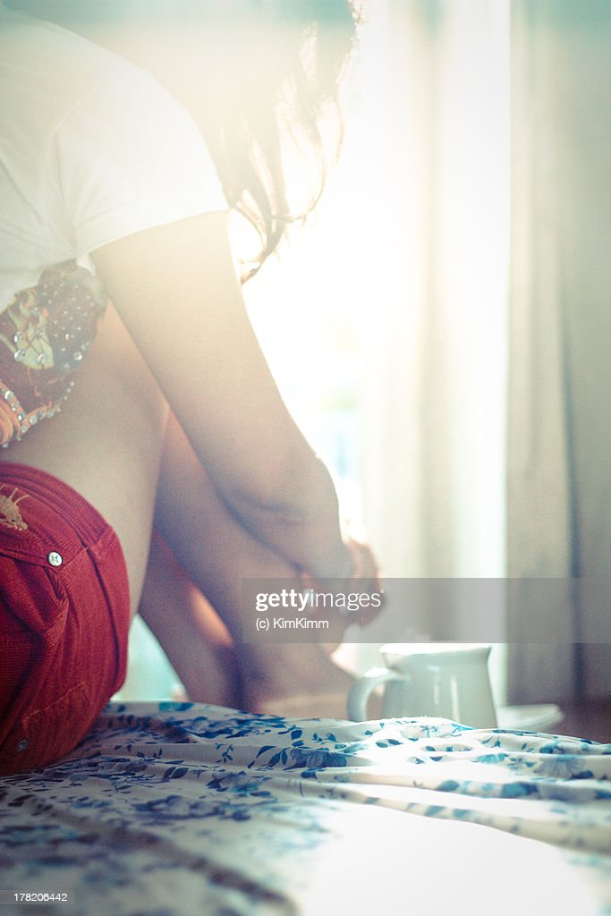 Girl sitting on bed and cup of tea in the morning : Stock Photo