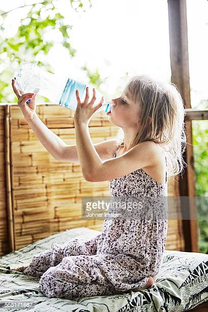 Girl sitting on bed and drinking water