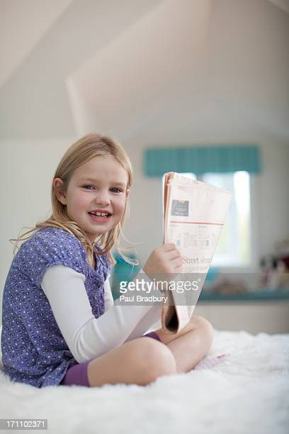 Girl sitting on bed reading newspaper