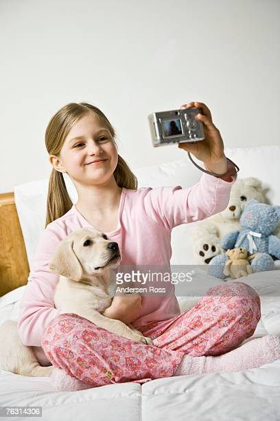 Girl (10-11) sitting on bed with puppy dog, taking self-photograph
