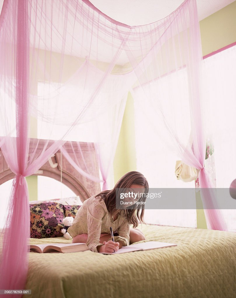 Girl (11-13) sitting on bed, writing on notebook : Stock Photo