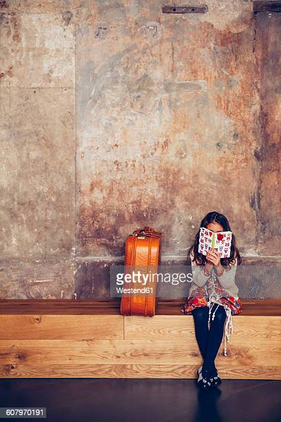 Girl sitting on bench reading book next to suitcase