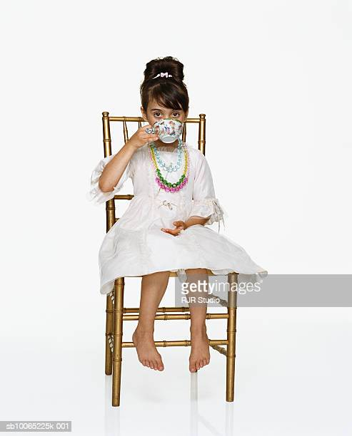 Girl (6-7) sitting on chair drinking tea, portrait, close-up