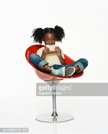 Girl (6-7) sitting on chair, eating peanut butter sandwich, portrait : Stock Photo