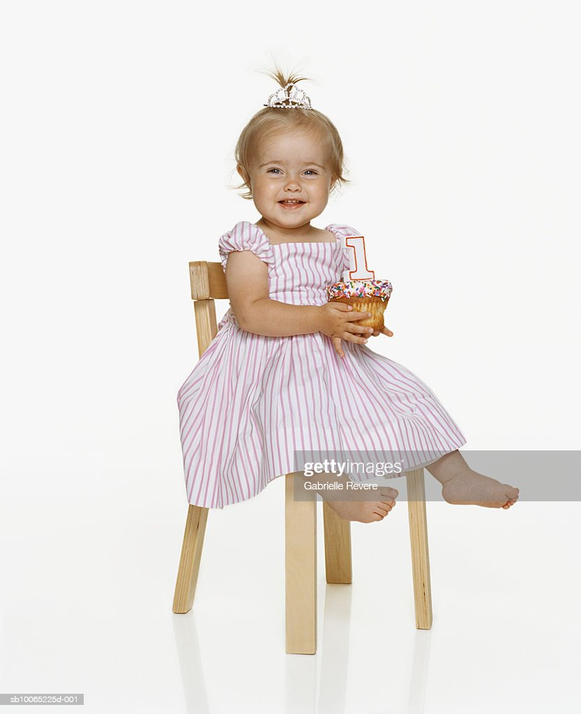 Girl (21-24 months) sitting on chair holding birthday cupcake, smiling