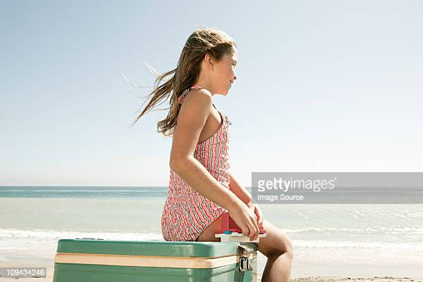 Girl sitting on coolbox on beach