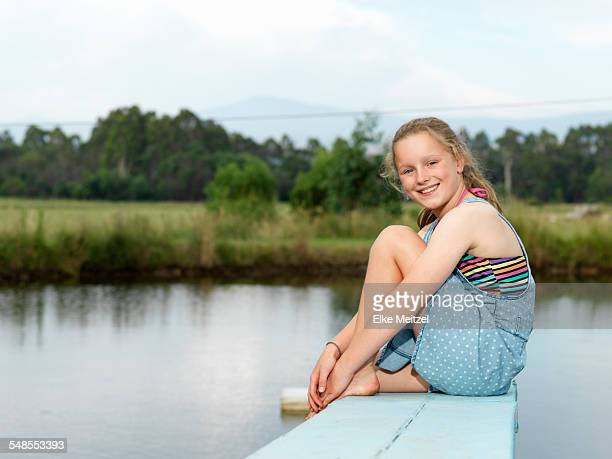 Girl sitting on diving board over lake