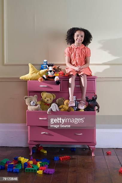 Ragazza seduta su cassettiera di giocattoli