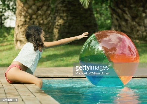 Pool Water With Beach Ball girl sitting on edge of pool reaching for beach ball in water