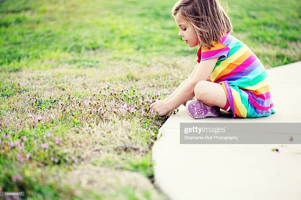 Girl Sitting on Edge of Sidewalk Picking Flowers : Stock Photo