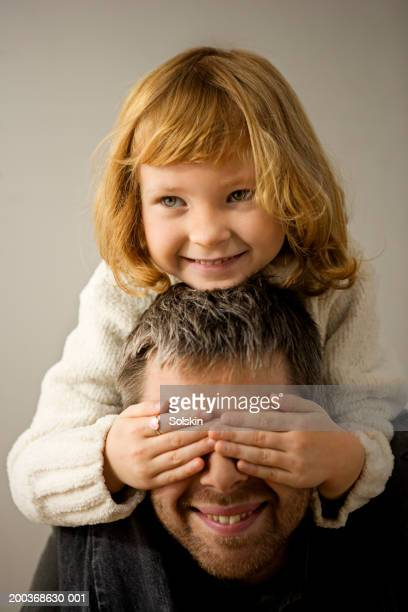 Girl (4-6) sitting on father's shoulders, covering his eyes, smiling