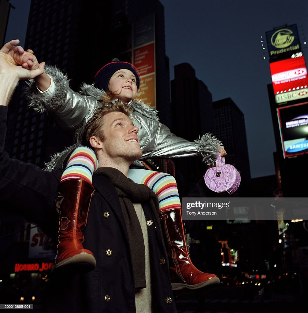 Girl (4-6) sitting on father's shoulders, sightseeing, night : Stock Photo