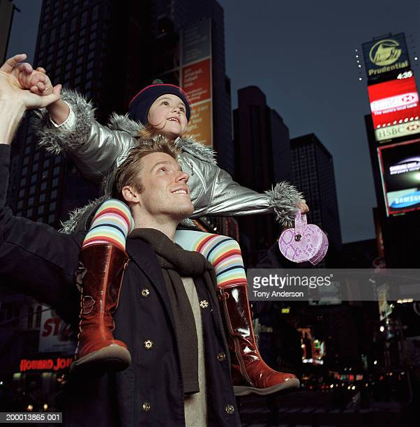 Girl (4-6) sitting on father's shoulders, sightseeing, night