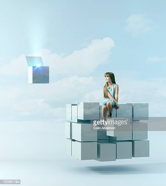 Girl sitting on floating cubes watching one open
