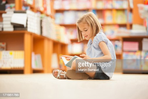 Girl sitting on floor of library with book : Photo