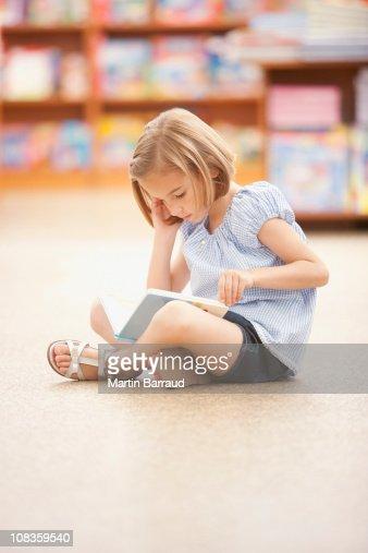 Girl sitting on floor reading book : Stock Photo