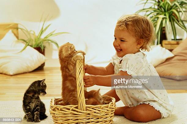 Girl (1-3) sitting on floor,playing with two kittens in wicker basket